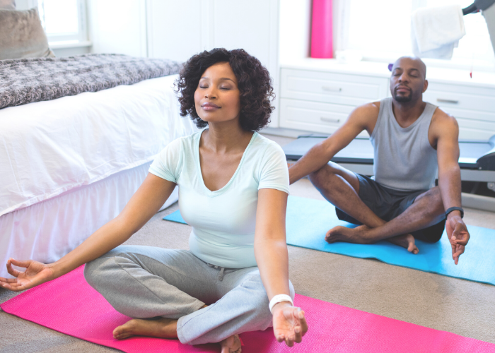 Black female and male meditating in their bedroom
