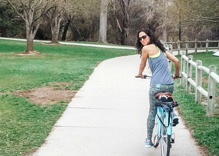 girl riding her bike on a bike path looking back at the camera