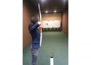 woman shooting a bow and arrow at a target inside a range