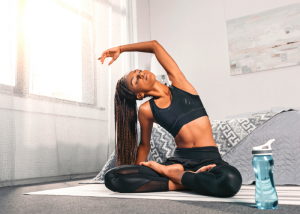 black woman doing a sitting side stretch yoga pose in her bedroom