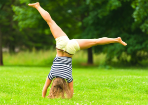 female doing cartwheels outside in the grass