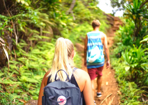 a man and woman going on a hike on a lush green path