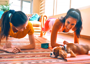 2 women doing a plank challenge together and smiling