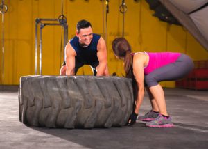 woman flipping a large tire at the gym as exercise
