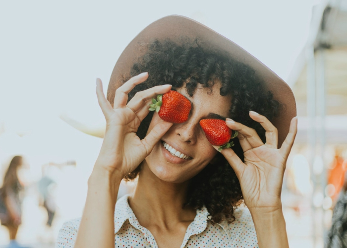 curly haired girl wearing a hat holding strawberries over her eyes