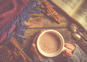 hands holding a cup of warm cacao next to an open book